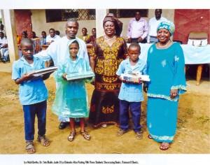 Iya Ndoh Bertha, Dr Tata Okolle Justin & Iya Balemba Alice Posing with Three Students Showing Books and Raincoats