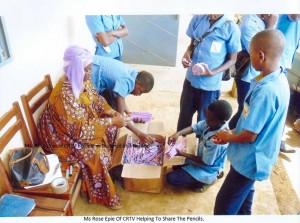Ms Rose Epie of CRTV Helping to Share Pencils among Students