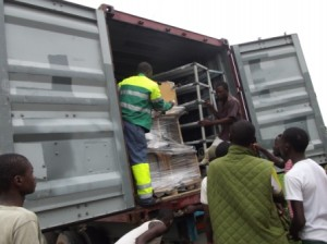 Oroko youths offloading medical supplies from the container
