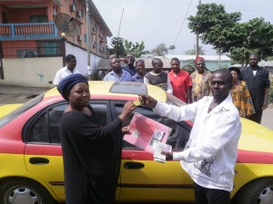 Buea Branch Manager of Raven Green, Asaah (L) hands over car keys & documents to the beneficiary, Gabuin