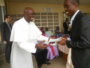 Rev.Fr Nkeze (L) awards a scholarship package to a deserving student of UIDB