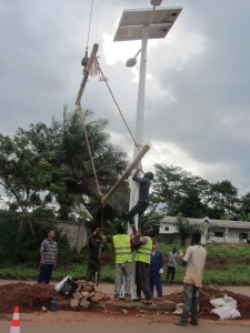 Workers install solar energy pole