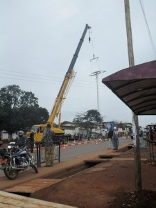 Workers mount solar energy pole on the Soa-Ngousso highway as pedestrians watch