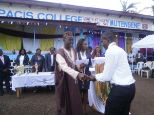 Gabriel Njikang(L) Representative of the Delegate of Secondary Education hands a prize to a student