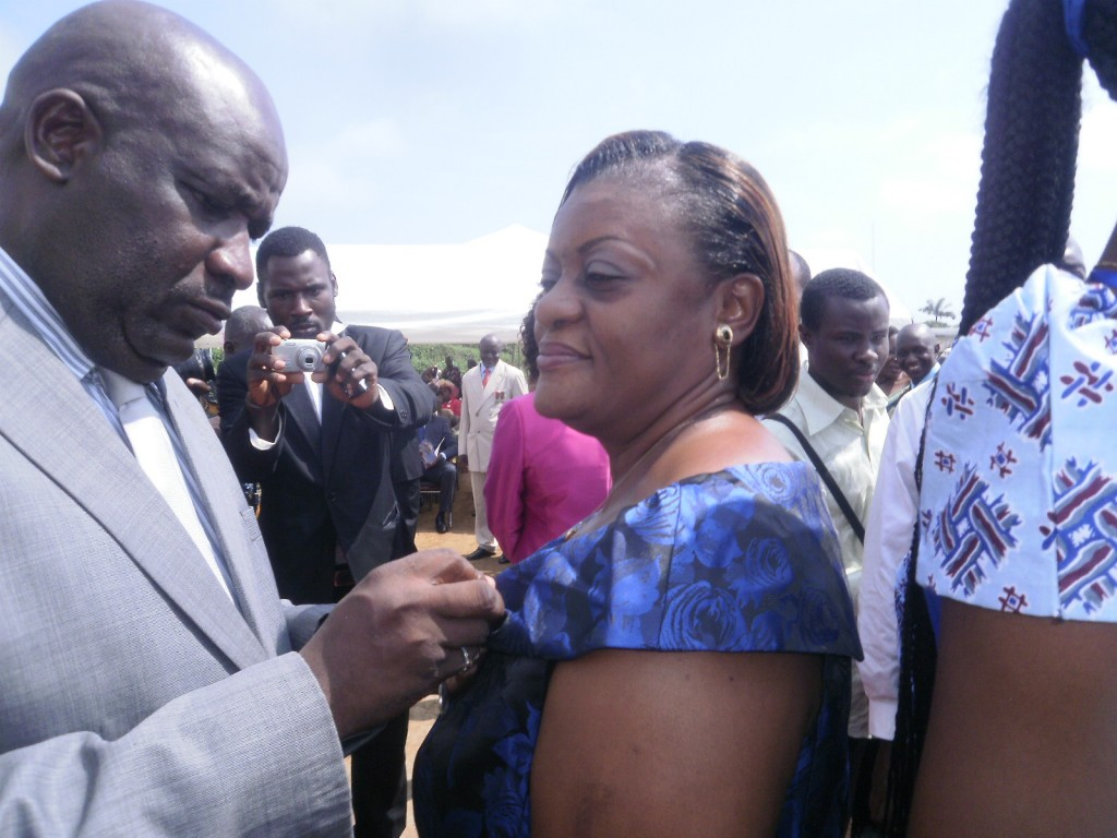 SDO of Fako Division, Zang III decorates Gwendoline Nkwantah, staff of the Board with a Bronze and Silver medals