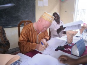 Fidelis Njie Ewumbue, Director, Borstal Institute, putting pen on paper at the MOU ceremony