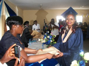 Comfort Kamara (L) of NEF, Limbe hands a prize to a deserving student of HIBMAT