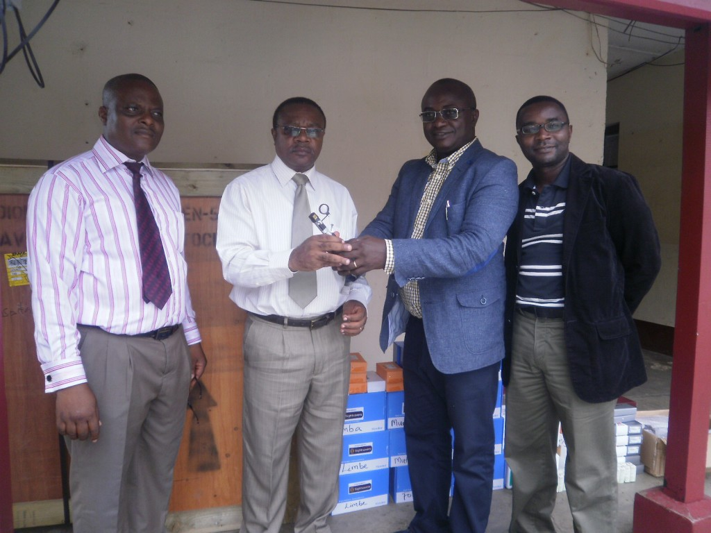 Southwest Regional Delegate of Health, Dr Mbome Njie(2nd from left) receives  sample of equipment from Dr. Oye(in blue jacket)