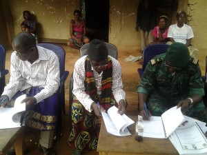 L-R Divisional Officer of Toko, Chief of Esukutan village & Conservator of KNP put pen on paper.