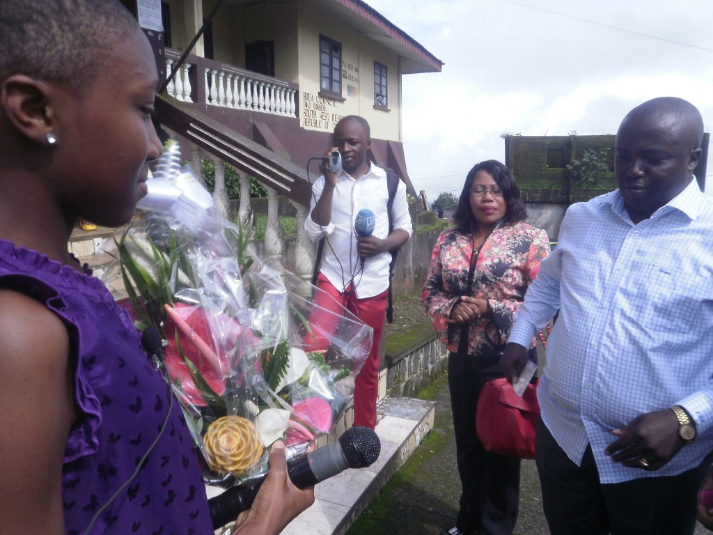 A daughter of Stranger Quarter (L) offers a bouquet of flower to Buea Mayor, Ekema (R) as he arrives in the neighbourhood