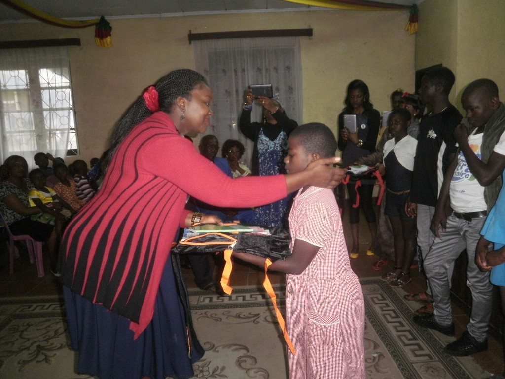 Councillor Stella Njoh presents back to school gifts to a pupil in Stranger Quarter
